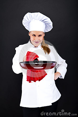 Young woman chef with tools on dark background