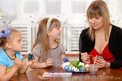Young woman with children paints an Easter egg