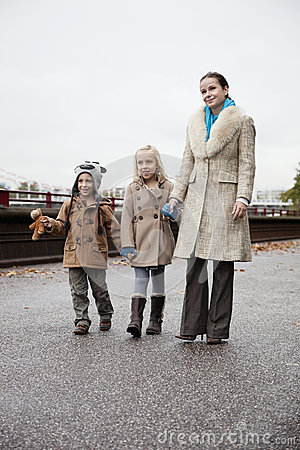 Young woman with children in warm clothing walking together on street