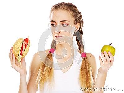 Young woman choosing between hamburger and apple