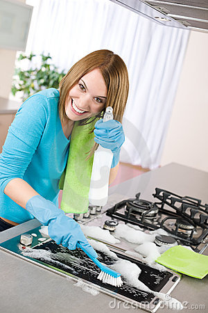 Free Young Woman Cleaning Stove In Kitchen Stock Images - 13938874