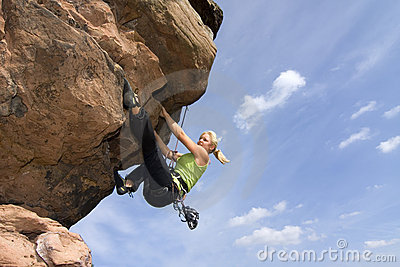 Young woman climbig a rock