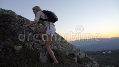 A young woman climbs a high rock at sunset or at dawn. Slow motion stock footage