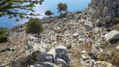 Young woman climbs a rock while trekking outdoors. Mediterranean coast stock video footage