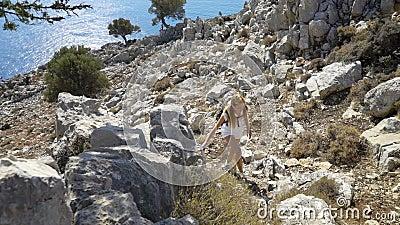 Young woman climbs a rock while trekking outdoors. Mediterranean coast stock video