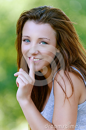 Young woman close-up puts finger