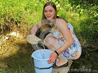 Young woman collecting water from natural spring Stock Photo