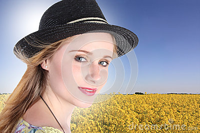 Young woman with colza field in background