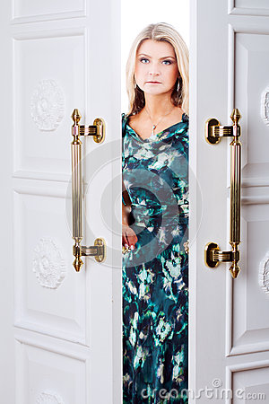 Young woman comes out of the door