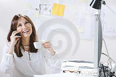 Young woman creative designer talking with phone while drinking a coffee