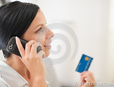 Young woman with credit card and speaking mobile