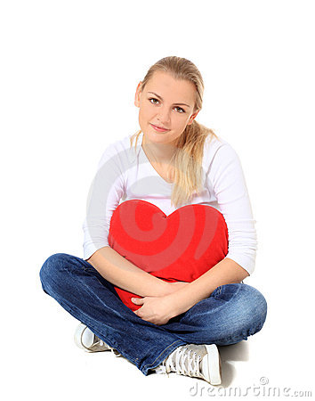 Young woman cuddling heart shaped pillow