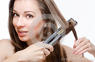 Young woman curling hair with hair straightener
