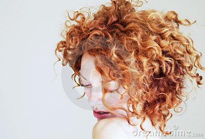 Young woman with curly red hair being shy