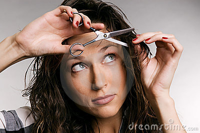 Young woman cutting her fringe