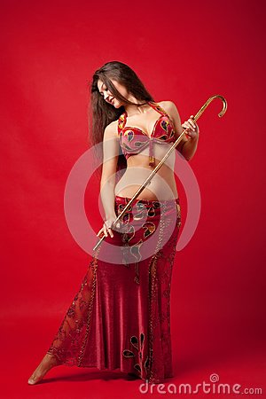 Young woman dance with cane in red arabic costume