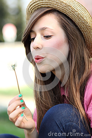 Young woman with a dandelion