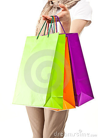Young woman demonstrating multicolored paper bags