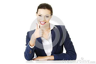 Young woman at the desk gesturing OK