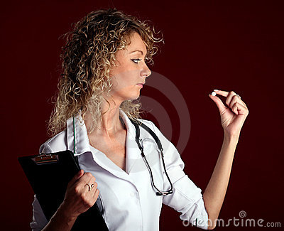 Young woman doctor with a pill