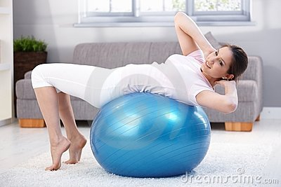 Young woman doing fit ball workout smiling