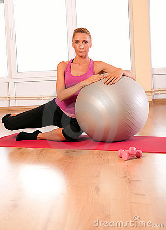 Young woman doing fitness exercise with fit ball.