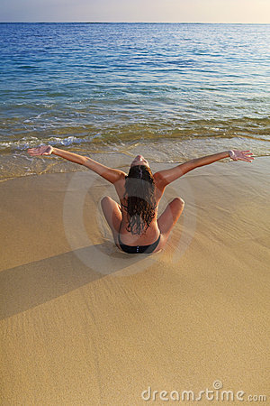 Young woman doing yoga at the beach
