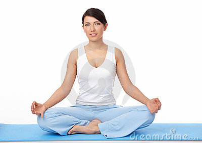 Young woman doing yoga exercise on blue mat