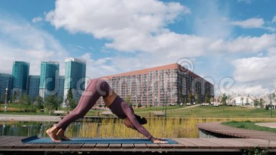 young woman doing yoga exercises with city on background