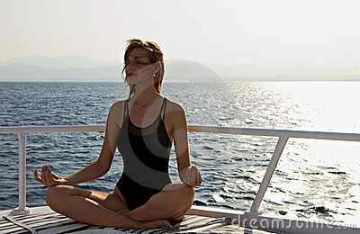 Young woman doing yoga meditation lotus position
