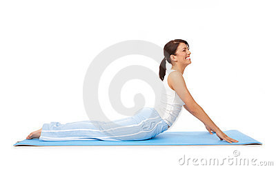 Young woman doing yoga or pilates  exercise on mat