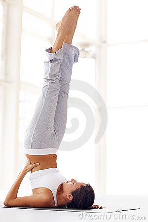 Young woman doing a yoga pose with feet in the air