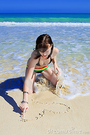 Young woman drawing in the beach sand