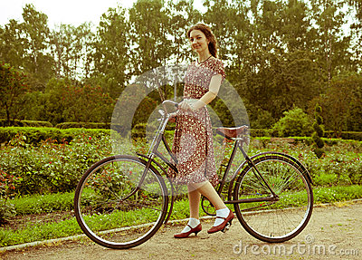 Young woman in dress posing with retro bicycle in the park.