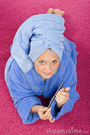 Young woman dressed blue bathrobe and towel filing nails