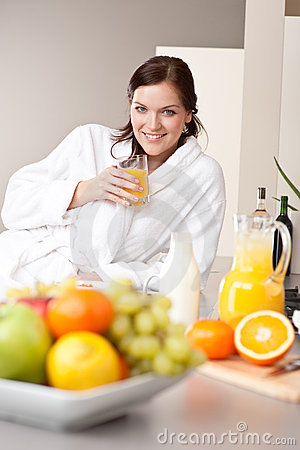 Young woman drink orange juice in kitchen