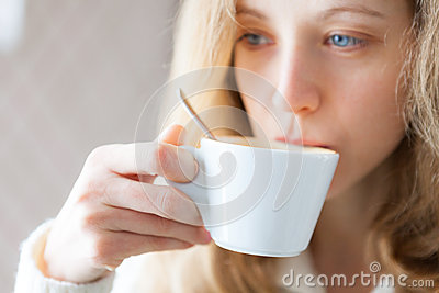 Young woman drinking coffee. Cup of hot beverage