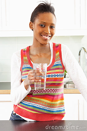 Young Woman Drinking Glass Of Water In Kitchen