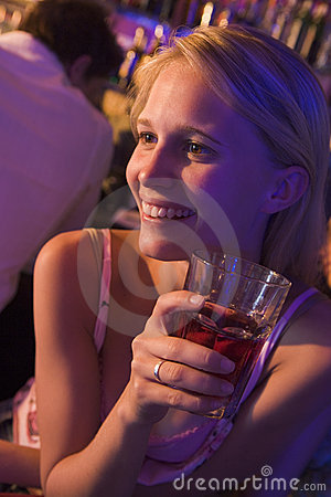 Young woman drinking at a nightclub