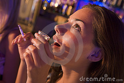 Young woman drinking shots and smoking