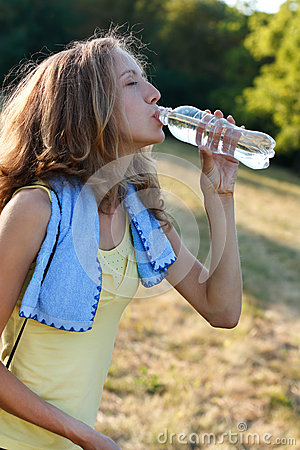Young woman drinking water after fitness workout