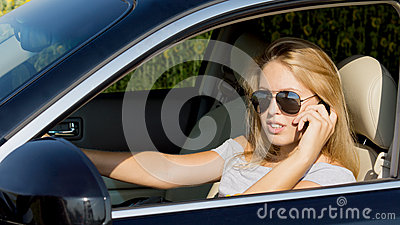 Young woman driver on her mobile