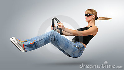 Young woman driver in sunglasses with a wheel