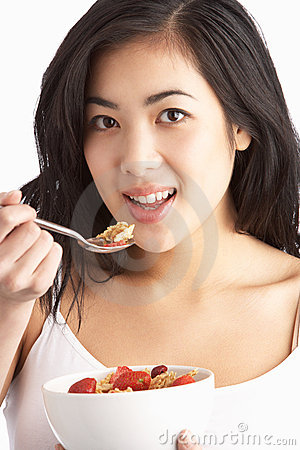 Free Young Woman Eating Bowl Of Cereal In Studio Stock Photography - 14456432