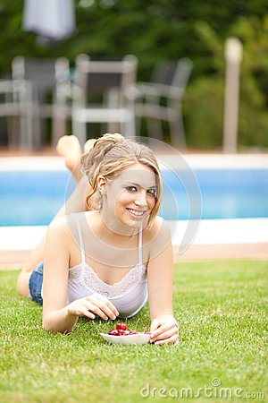 Young woman eating a cherries on the grass