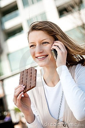 Young woman eating chocolate on the phone