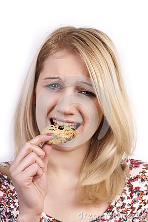 Young woman eating cookie with grimace