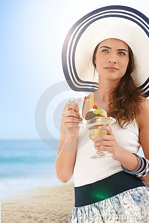 Young woman eating icecream on summer beach
