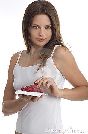 Young woman eating raspberry