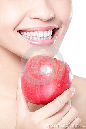 Young woman eating red apple with health teeth